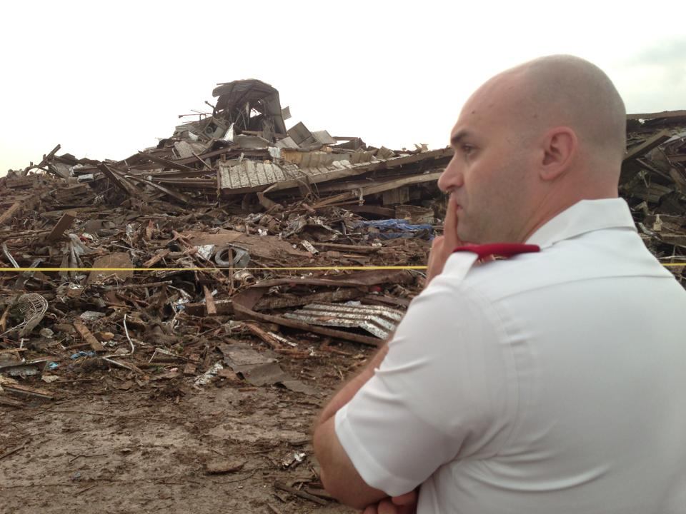 Salvation Army Officer looks over damage