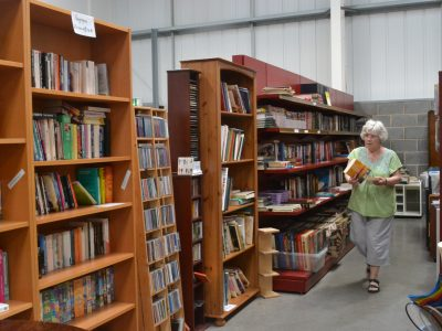person walking by book shelves