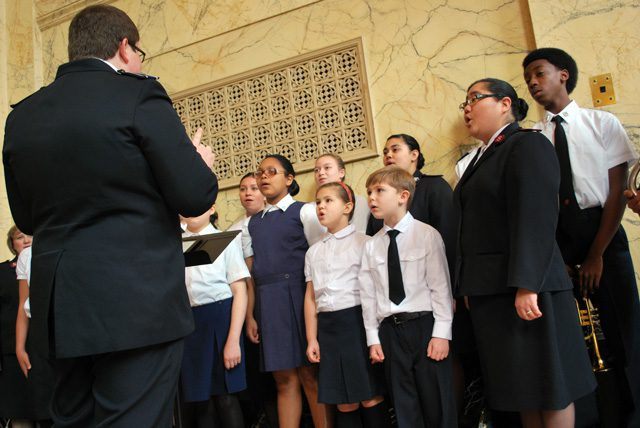 """Zane Morris leads the Portland Tabernacle singing company in the lobby of the Arlene Schnitzer Concert Hall prior to """"Something Grand."""" Lt. Jennie Onitsuka-Adams, assistant corps officer at Portland Tabernacle, lends her voice to the choral group."""