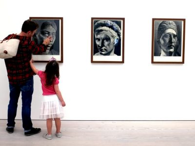 Father and daughter looking at painting