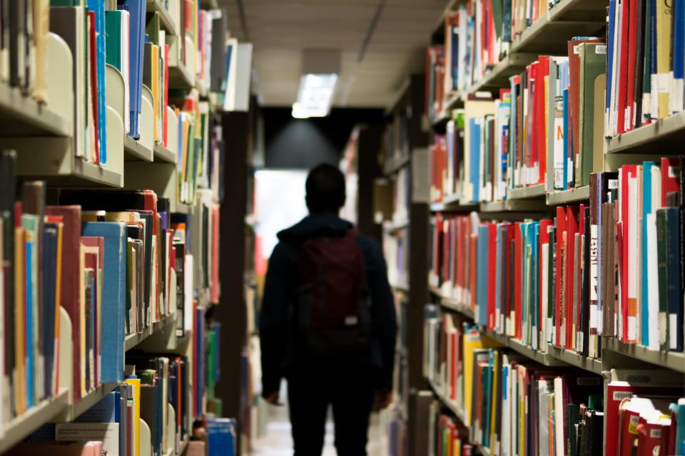 Person Walking between shelves in library
