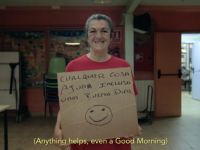 Homeless woman smiling with cardboard sign