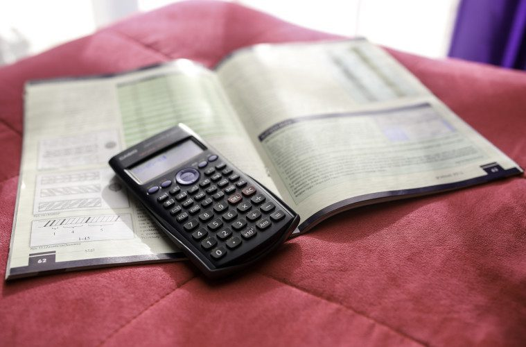 textbook and calculator on blanket