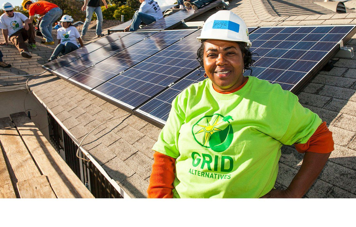 Woman in green shirt and hardhat next to solar panel
