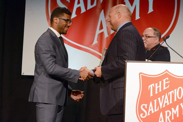 Russell Wilson accepts an award from Arthur K. Langlie at the Red Kettle Luncheon in Seattle.