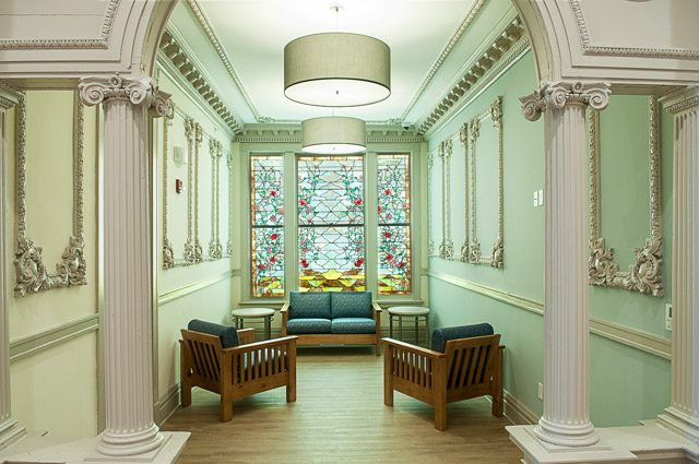 third floor casual sitting area featuring intricate stained glass landscape, c. 1907.