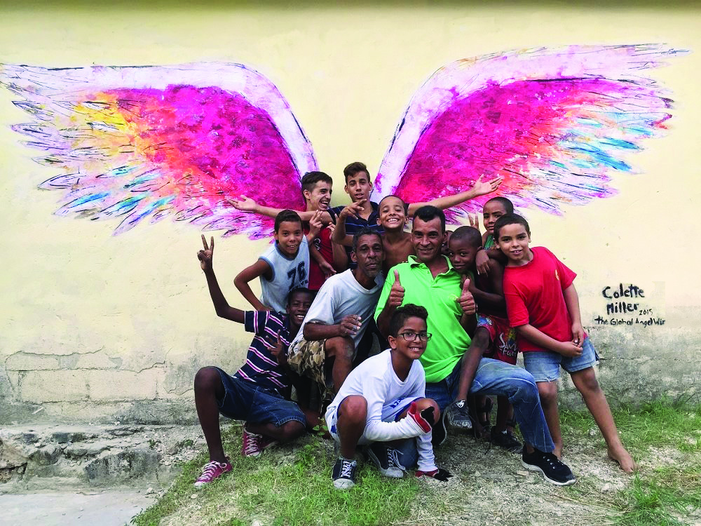 People posing in front of angel wings