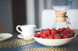 Bowl of strawberries next to coffee cup