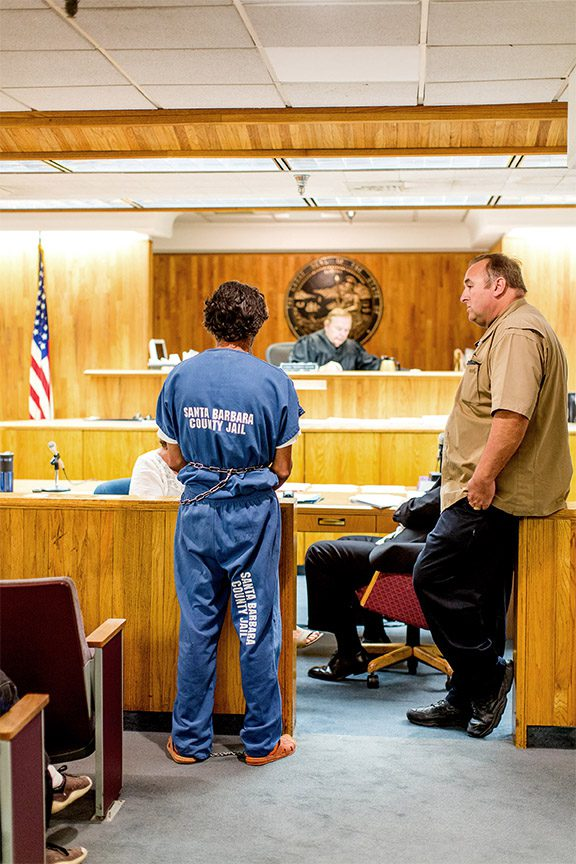 Person in prison jumpsuit in courtroom