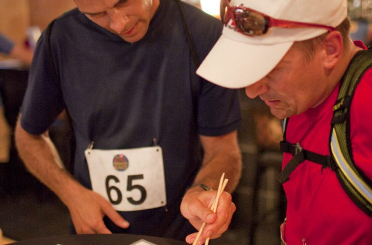 two men eating with chopsticks