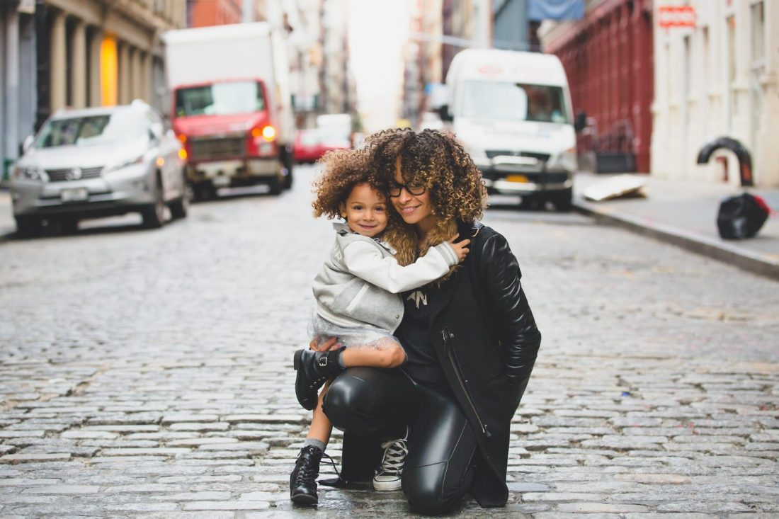 Mother and Daughter hugging in street