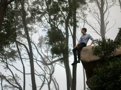 Man sitting on edge of cliff