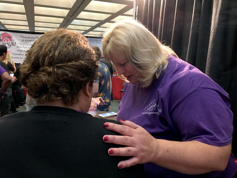 A volunteer prays with a visitor to The Salvation Army's AdultCon booth.   Photo by Jackeline Luna