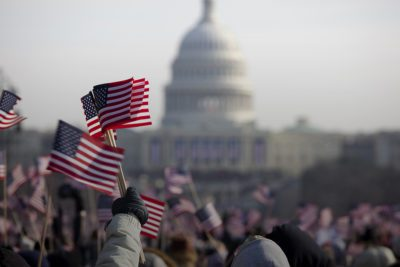 People waving miniature flags at the capitol building