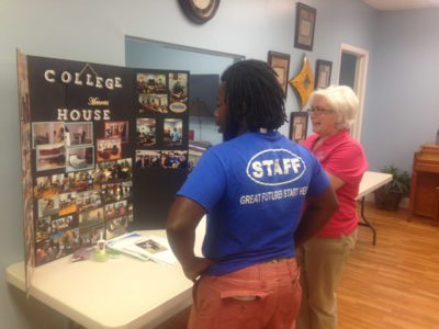 Jerry Bazilme, 21, and Captain Teresa Della Monica look at collage of pictures of students involved in The Salvation Army's student housing program in Tampa, Fla. In addition to discounted housing, the program also grants students access to the College Student Center and other resources.