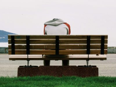 Person sitting on bench with head down