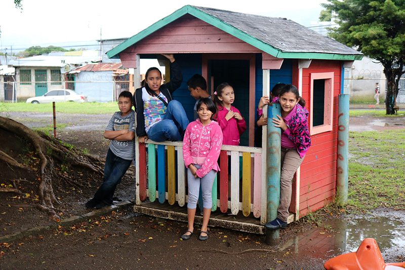 Children standing outside playhouse