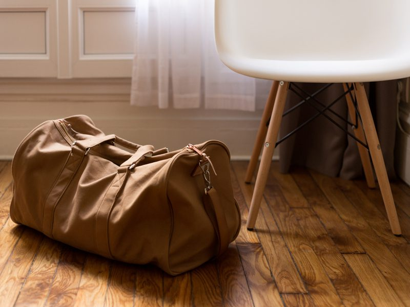 Duffel bag on ground next to chair