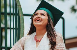 young woman in graduation cap smiling outside