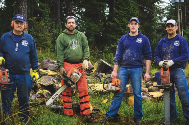 Four men outside with chainsaws