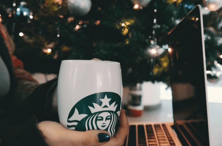 Hand holding cup with laptop on lap next to Christmas tree