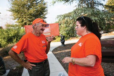 Ronnie Wald, an 81-year-old veteran resident of The Salvation Army Bell Shelter, talks with a Team Depot volunteer during a transformation of the shelter this fall.