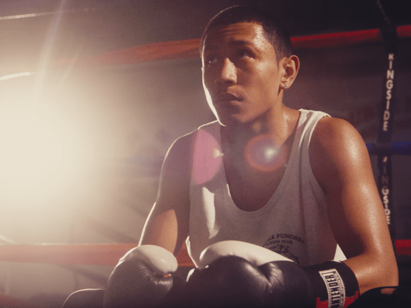 younger boxer looking focused sitting in ring