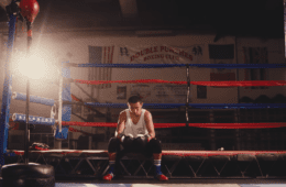 young boxer sitting on ropes inside ring