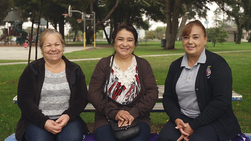 Three women sitting on bench outside smiling