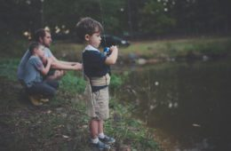 Child holding camera by pond