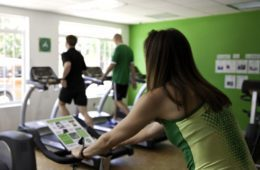 people exercising on treadmills and stationary bike
