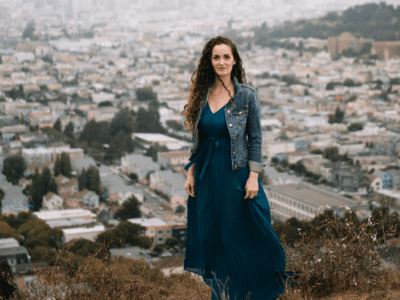 Woman standing on hill above city