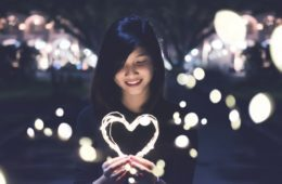 Girl smiling while holding illuminated heart