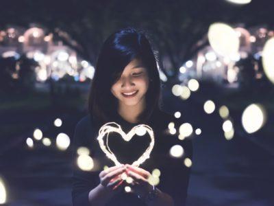 Girl smiling while holding illuminated heart