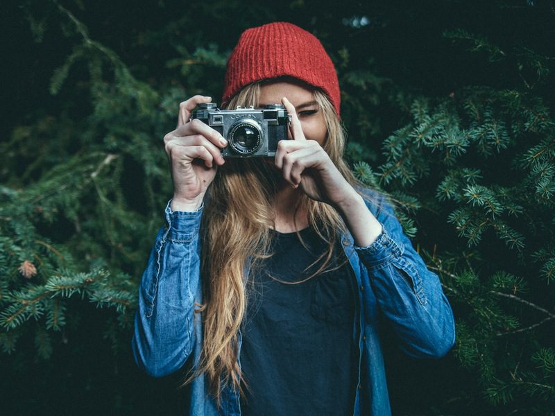 Woman in red beanie and blue jacket holding camera