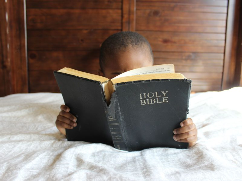 child reading bible on bed