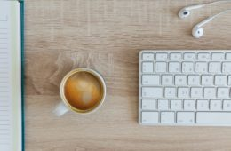 Coffee on table next to keyboard and headphones