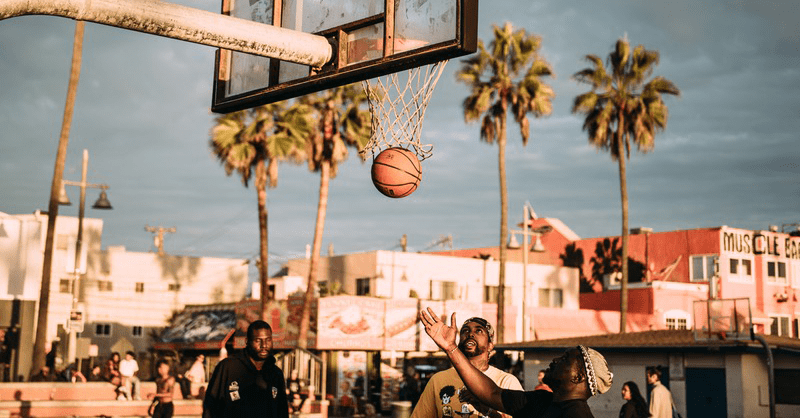 Men playing basketball during daytime