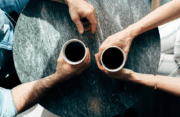 Two people at a table holding cups