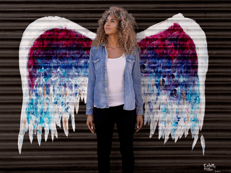 Angel wings painted on wall with woman posing