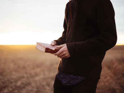 Person holding Bible outside