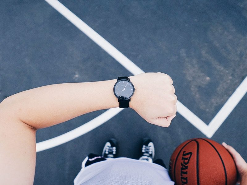 Person looking at watch with basketball in other hand