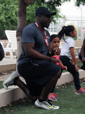 Fitness coordinator stretches with kids