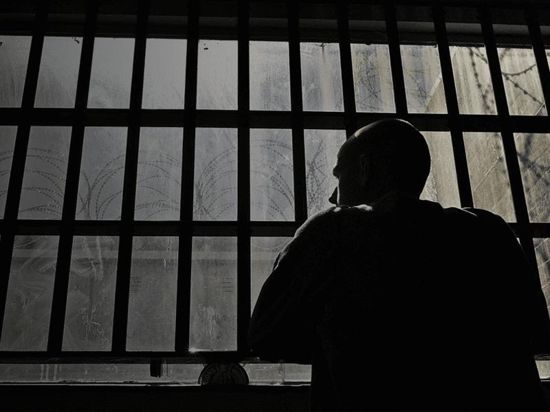 Man looking out window in dark room