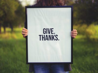 Person holding sign that says give thanks