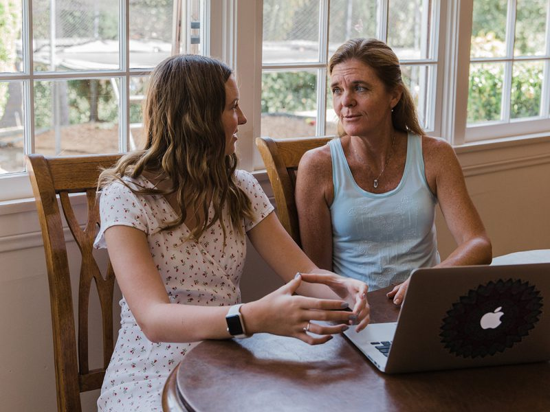 Mother and daughter sitting at table and talking in front of computer