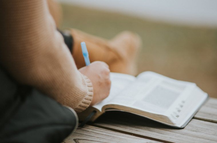 person with pen and Bible