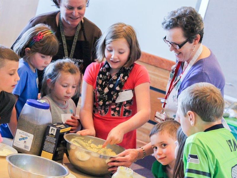 Adults helping kids cook