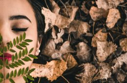woman laying with eyes closed next to leaves