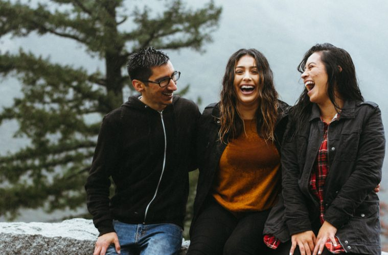 Three people laughing together outside